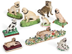 Lot 54 NINE PORCELAIN AND POTTERY MODELS OF PUG DOGS  CIRCA 1755-1890, INCLUDING MILTON AND DERBY, IMPRESSED AND PAINTED MARKS Comprising: a Derby example seated on a green and puce-edged base, a smaller example similar, an English porcelain example on a flower-encrusted long base, another recumbent on a purple cushion, a continental porcelain example, two honey-coloured examples on green mound bases and two pearlware examples seated on tasselled cushions The pug on flower-encrusted base 9 in. (23 cm.) long overall (9) Estimate: £2,000 - 3,000