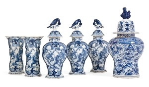 LOT 24 A DUTCH DELFT GARNITURE OF BLUE AND WHITE VASES AND A VASE AND A COVER  LATE 18TH CENTURY  The garniture painted with reserves of a Chinese garden, with parrot finials, the single vase painted all over with flowers and birds The single vase 18 in. (45.7 cm.) high (6) Estimate:£1,500 - 2,500