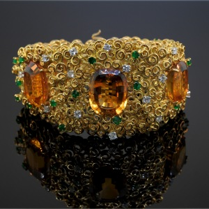 AnEnglish 18 karat textured yellow gold wide bracelet set with citrines, emeralds and diamonds by Andrew Grima, 1967. From Lucas Rarities