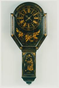 Thomas Chappell - Tavern clock An exceptionally rare George II period shield dial Tavern Clock of most unusual elongated form, the 8 Day movement with rectangular shaped plates. On the dial below the chapter ring are two outer angels playing trumpets and a central angel holding a scythe and an hour glass. The chinoiserie decoration on the door is also very distinctive with sun and clouds at the top and an intimate dining scene below. Date: circa 1755 Height: 64 in (165 cm)