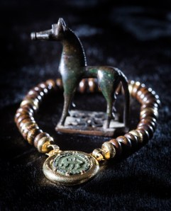 Kallos Gallery: A bronze horse votive of the geometric era (750-730BC). Price on application A 'regardant beast' motif on a disc brooch found in East Anglia, on a necklace with bronzites.  Price on application​ Credit: 'Ka​llos Gallery and Alex Brenner'