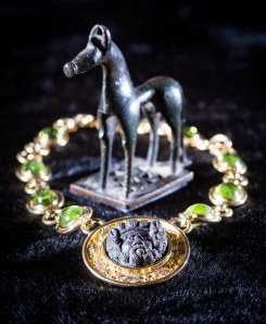 Kallos Gallery: A bronze horse votive of the geometric era (750-730BC). Price on application An 18ct yellow gold necklace with 9 oval cabochon peridots, with an ancient bronze Zeus.  Price on application Credit: 'Ka​llos Gallery and Alex Brenner'