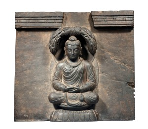 SEATED BUDDHA Gandhara, 2nd/3rd century Height: 32 cm Width: 29 cm Depth: 8 cm A carved grey-brown schist architectural element formed as a square tile and with a relief sculpture of a seated Buddha to its centre, framed above by two horizontally carved stepped sections also in relief and separated to the middle by a dovetailed void. Simon Ray Ltd