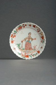 Lot 325 - A rare Chinese porcelain Dutch-decorated South Sea Bubble saucer  early 18th century, with moulded rim, enamelled in Holland c.1720 with a lady holding a spade and standing before a piece of paper on the ground, bearing the inscription 'Het is Wint', a feather falling from her left hand, the rim with flowering branches of prunus and peony, 13.5cm. Together with a British Museum, Prints and Drawings, photograph of a print of a pack of 18th century playing cards (see footnote). (2) Provenance: the Helen Espir Collection, no. 873. Purchased from E & H Manners, April 2003. Illustrated: Helen Espir, European Decoration on Oriental Porcelain, pp.155 and 156. This satirical reference to the foolishness of investors in the South Sea Company implies that this lady's shares are as 'light as a feather', i.e. worthless. The decoration derives from a pack of playing cards published in Amsterdam in 1720, this particular lady being the Queen of Spades, depicted as Madame Quincampoix. Estimate: £600 – 1000