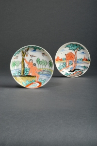 Lot 345 - Two Chinese porcelain Dutch-decorated saucers  1st half 18th century, originally left in the white and later-enamelled in Holland, one with a scene of Adam and Eve beneath the Tree of Knowledge, the serpent offering the apple to Eve while birds fly above, the other decorated with a tall dovecote beneath a tree, a church and other European buildings beyond, 11cm. (2) Provenance: the Helen Espir Collection, nos. 896 and 925. Illustrated: Helen Espir, European Decoration on Oriental Porcelain, p.197, pl.54 for the Adam and Eve saucer. The enamel palette of both saucers is distinctly Dutch, and the subject of the first couple a traditional theme for Delft chargers. Estimate: £600 – 1000