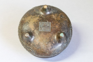 is  A Chinese bronze censer for the Islamic market, squat globular form with everted rim on three feet, decorated with mirror form cartouches of Islamic script on a ring punched ground, six character seal mark to base, 14.5cm diam approx.,