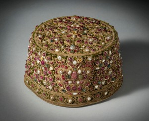 Jewel encrusted Muslim Royal Cap Mughal style, made by Ezra & Sion Co, Bombay, early 20th century Green velvet cap, embroidered with twisted gold thread, gold sequins and encrusted with pearls, rubies, spinels and emeralds. Lined in satin and edged inside in leather around the base of the cap. Stamped on leather 'Primus' 'Ezra & Sion Co., 95-97 Ghendy Bazaar, Bombay' 'Perfect Ventilation - Latest Combination' Height: 10 cm; Diameter: 15.5 cm Francesca Galloway Ltd
