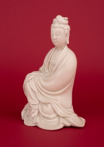 Guanyin, seated with her hands covered by her long flowing robes above her raised right knee with one foot exposed, her hair neatly tied and pinned with a ruyi-head pin and lingzhi diadem, with serene features, elongated earlobes and urna mark on her forehead and wearing a lotus flower head necklace, covered in a cream glaze. The back with an impressed double gourd mark of He Chaozong. 9 1/4 inches, 23.5cm high. Ming dynasty, circa 1630. Carved openwork wood stand with rockwork, pine and lingzhi. Formerly in the Collection of Captain Meuldijk, the Netherlands. Marchant & Son