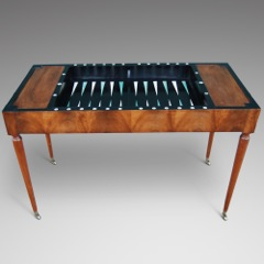 A walnut veneered French trice/trac or games table, the removable top with a leather inlaid writing surface to one side & green baize games surface to the reverse enclosing an ebonised backgammon board with natural & green stained ivory inlay Geoffrey Stead