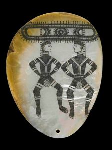 Pearl shell pendant with dancing figures.  Kimberley region, Western Australia, before 1926.   Pearl shell, charcoal  © The Trustees of the British Museum.
