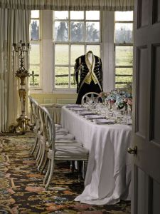 A View of the Morning Room, showing a table setting, the Axminster Carpet (Lot 51) and a male servant's livery.