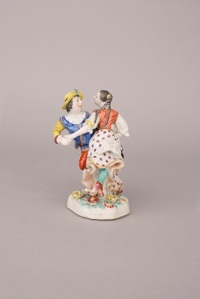 Famille rose figural group of a dancing couple, modelled after the Meissen original, the gentleman wearing a yellow hat, white-ruff collar, blue waist jacket incised with scrolls and red breeches, the lady with a red waist coat similarly incised and long flowing skirt with purple flowers, all on a shaped naturalistic form base, modelled and moulded with relief flowers. 5 ⅝ ins, 14.3 cm high Qianlong, circa 1752. Marchant