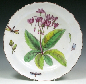 Dodecatheon meadia: A plate with a wavy brown-edged rim, painted with a Dodecatheon Meadia, two seed heads, an immature seed head and three flying insects. c. 1755-57                                        Mark: red anchor, Diam: 21.6 cm Private Collection