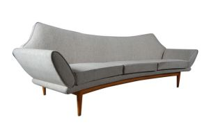 A freestanding three seater sofa with Oak frame. Newly upholstered in a cream cotton fabric with original sprung back and seat cushions, designed by Danish architect Johannes Andersen, manufactured 1950-60s by Trensum, Sweden,  Omnipod.  Courtesy Olympia International Art & Antiques Fair.