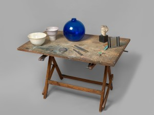 Table with blue glass vase, beach pebble on stand, African sculpture on lacquered base, Greek torso on marble base, two ceramic bowls and one small wooden easel