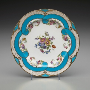 Factory: Sèvres Porcelain Manufactory Painted by: Jean-Baptiste Tandart  (active 1754- 1803) Plate: Part of a Dessert Service with Flowers and Turquoise Blue Ribbons, 1782 Soft-paste porcelain 1 x 9 3/8 in. (2.5 x 23.8 cm) Henry Clay Frick Bequest Accession number: 1918.9.36