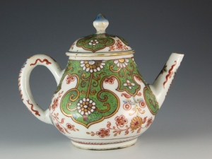 Juno Antiques Early London decorated small Chinese teapot and cover, enamelled with white flower heads on a green seeded ground, surrounded by red and gilt tramline cartouches, c.1740.