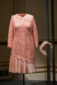 Crystal and lace peach beaded cocktail dress by Angela Kelly. The dress and headpiece were worn by The Queen when she appeared in the opening ceremony of the London 2012 Olympics with James Bond. Royal Collection Trust /© Her Majesty Queen Elizabeth II 2016.