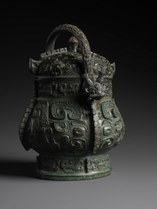 Archaic Bronze Wine Vessel and Cover (You) Shang or Early Western Zhou period, 11th century BC Height (to top of knop): 27.4cm Weight (without handle): 3.80kg Courtesy of Eskenazi