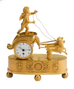 Rare French Empire ormolu mantle timepiece of chariot form with white enamel dial forming the wheel, surmounted by Amour being pulled by two dogs, c1810, from Richard Price.