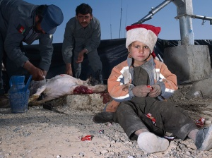 Mark Neville,- 'Child, Jacket, Slaughtered Goat, Sweets, Painted Nails, Xmas Day, Helmand', 2010, courtesy Mark Neville